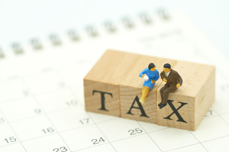 Miniature people Pay Annual income (TAX) for the year on Calendar using as background business concept and finance concept with copy space  for your text or  design. Stock Photo