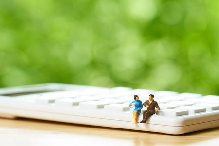 Miniature two people sitting on white calculator using as background business concept and teamwork concept with copy space and white space. Kho ảnh