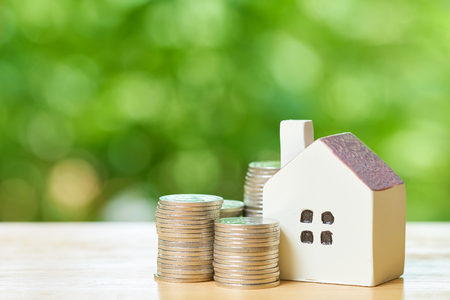 a model house model is placed on a pile of coins.using as background business concept and real estate concept with copy space for your text or design. Kho ảnh