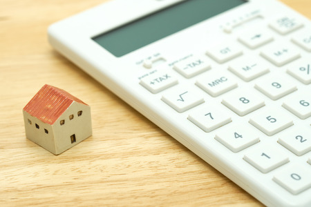 A model house model is placed on a calculator. as background property real estate concept with copy space for your text or  design.