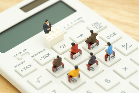 Miniature people Pay queue Annual income (TAX) for the year on calculator. using as background business concept and finance concept with copy space  for your text or  design.