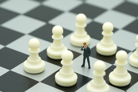 Miniature people businessmen standing on a chessboard with a chess piece on the back Negotiating in business. as background business concept and strategy concept with copy space. Kho ảnh