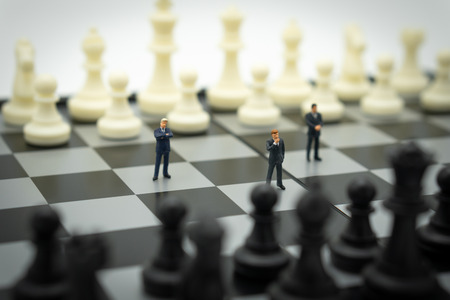 Miniature businessmen standing on a chessboard with a chess piece on the back. as background business concept with copy space.
