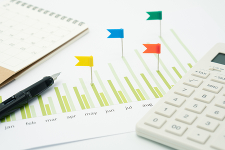 Calculators and pens put on stock chart Investment Analysis Or investment Sales rankings are targeted to determine the flag. using as background business concept with copy space and white space.