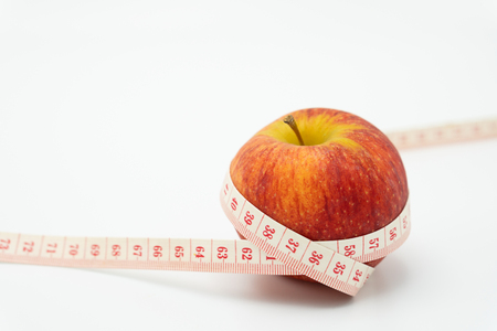 Red apple wrapped around with measure tape. Healthy fruit To control the weight and skin. as background Diet concept and healthy concept with copy space. Stock Photo