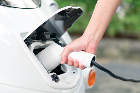 Asian Women Bring Battery Chargers Connect with electric car To put the electric car into the car. Clean energy does not pollute the air. Energy conservation concept Alternative energy