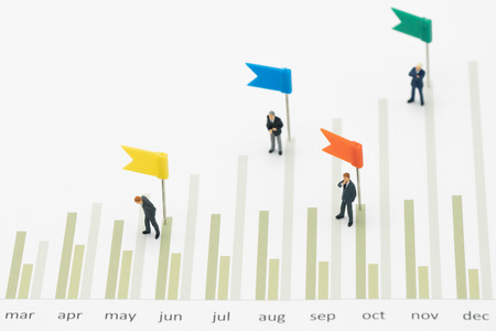 Miniature people businessmen standing Investment Analysis Or investment Sales rankings are targeted to determine the flag. using as background business concept with copy space and white space.