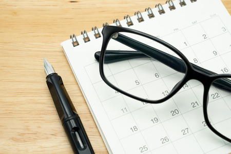 A Fountain pen and Black eye glasses spectacles is placed on a calendar. using as background business concept and finance concept with copy space  for your text or  design.