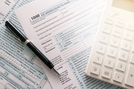 a pen to fill out an annual tax bill with a calculator to calculate the tax rate. as background business concept and finance concept with copy space  for your text or design. Stock Photo