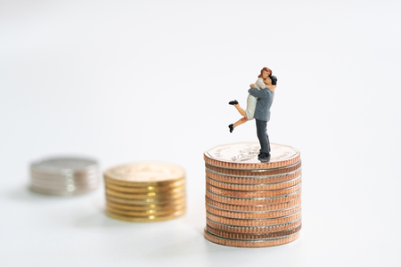 Couple Miniature 2 people standing on stack of coins to thinking and planning.as background real estate and family concept with copy space. Stock Photo