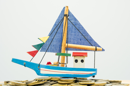 Model boat is placed on a pile of coins.using as background business concept and finance concept with copy spaces for your text or design. Stock Photo