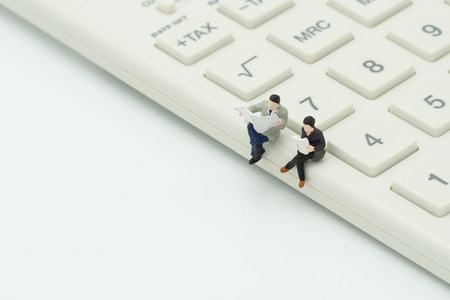 Miniature 2 people sitting on white calculator using as background business concept and teamwork concept with copy space and white space.