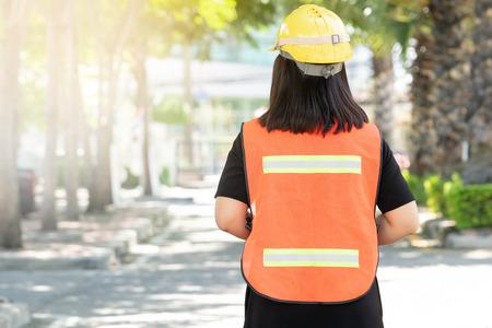 Le contremaître supervise les travaux de construction, porte des vêtements de travail réfléchissants pour la sécurité au travail. Le réflecteur a un réflecteur réfléchissant argenté et un kit réfléchissant vert pour une vue dégagée. Banque d'images