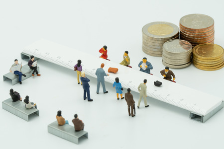 Miniature People use cash deposit. At the bank counter or financial institution. There are many users. as background business concept and Saving concept with  copy spaces for your text or design. Stock Photo