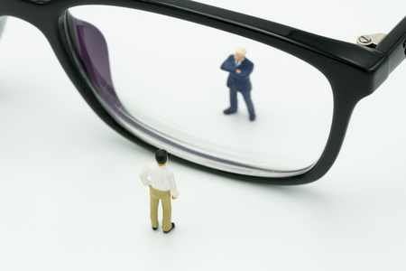 Miniature people businessmen standing Stand looking through your eyes, black frame. Reflections on future prospects. using as background business concept with copy space and white space.