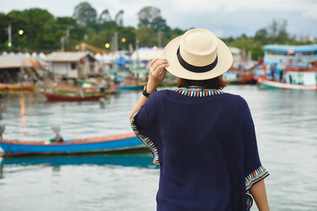 Young women asian wearing a hat, travel back pack View of the fishing harbor Sunset Latinos There is a boat landing. In a fishing village in Rayong, Thailand Stock Photo