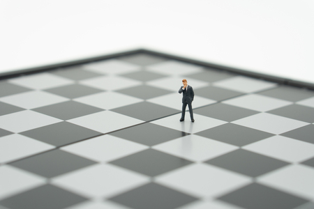 Miniature people businessmen standing on a chessboard with a chess piece on the back Negotiating in business. as background business concept and strategy concept with copy space. Stock Photo