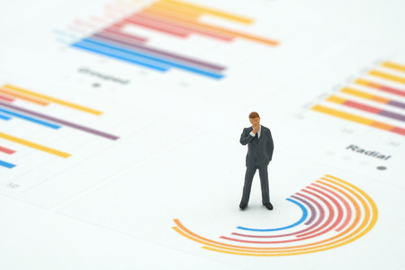 Miniature people businessmen analyze standing on Circle graph with performance as background strategy concept and Business concept with copy space. Stock Photo