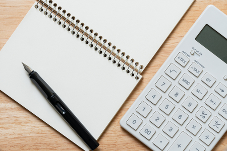A Fountain pen is placed on a notebook and calculator. using as background business concept and finance concept with copy space  for your text or  design. Kho ảnh