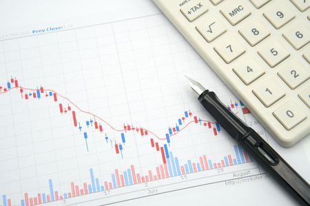 Fountain pen placed on the stock chart is the background Investment Analysis investment and white calculator using as background business concept and investment concept with copy spaces