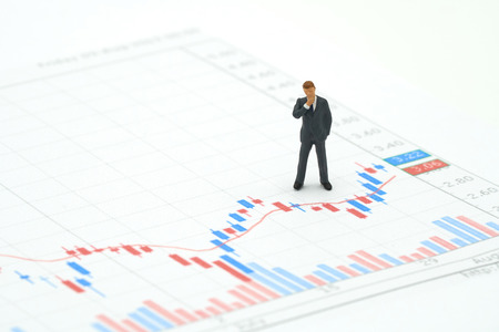 Miniature people businessmen standing on the stock market chart is the background Investment Analysis investment . using as background business concept with copy space and white space. Stock Photo