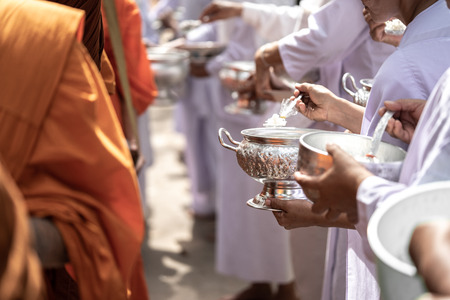 The monks of the Buddhist Sangha(give alms to a Buddhist monk), which came out of the Buddhist offerings in the morning. In order to demonstrate faith faithfully perform the duties recently. Фото со стока