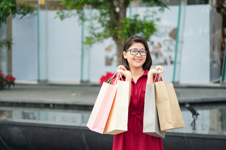 Beautiful girl holding a shopping bag. Many bags show a happy feeling. In the purchase. Shop at discount stores. The festival. Shopping concept Standard-Bild - 114602762