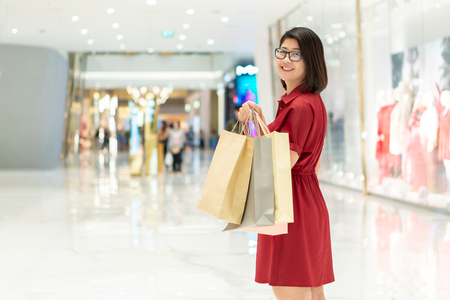 Beautiful girl holding a shopping bag. Many bags show a happy feeling. In the purchase. Shop at discount stores. The festival. Shopping concept Standard-Bild - 114602910