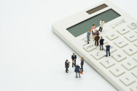 Miniaturowe osoby Kolejka płac Roczny dochód (podatek) za rok na kalkulatorze. przy użyciu jako tło koncepcji biznesowej i koncepcji finansów z miejsca kopiowania tekstu lub projektu. Zdjęcie Seryjne