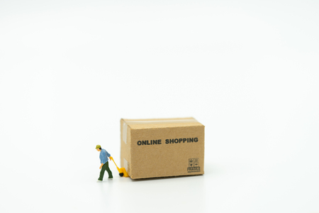 Miniature people Construction worker Online shopping with a shopping cart and shopping bags delivery service using as background shopping concept and delivery service concept with copy space Stok Fotoğraf