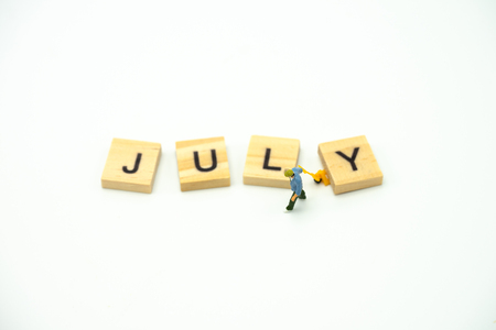 Miniature people Construction worker standing with wood word Month. using as background business concept and calendar concept with copy space  for your text