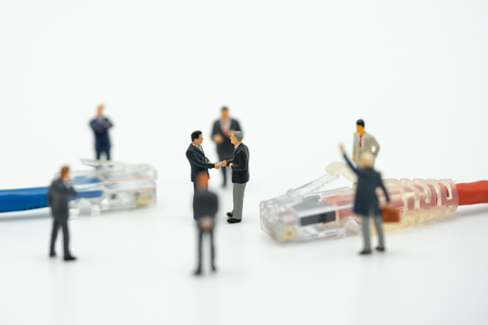 Miniature 2 people businessmen Shake hands on the back Negotiating in business. as background business concept and finance concept with copy space. Imagens