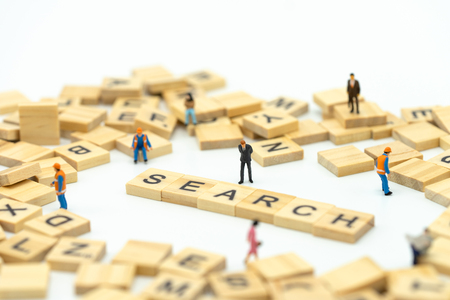 Miniature people businessmen standing with wood word SEARCH. Find something The answer to the solution.using as background business concept and finance concept with copy space  for your text Standard-Bild - 114603164