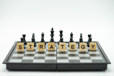 Wood word STRATEGY placed on chessboard with a chess piece on the back Negotiating in business. as background business concept and strategy concept with copy space. Standard-Bild - 114603201