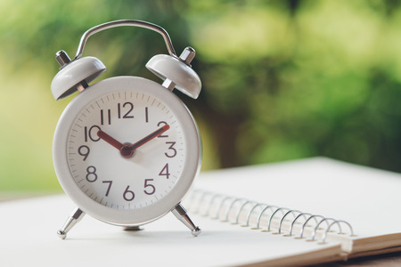Vintage White Alarm Clock on on a NoteBook. It's time to rest. using as background  Relaxing time concept with copy spaces for your Standard-Bild - 114603213