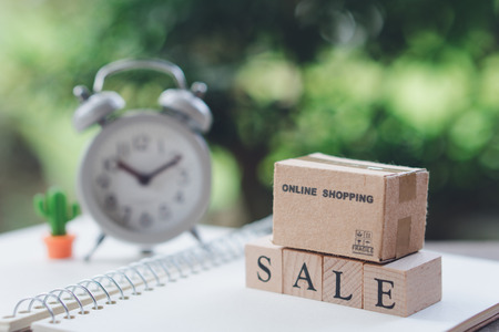 shopping bags placed on wood word SALE with Vintage White Alarm Clock using as background shopping concept and delivery service concept with copy space  for your text or design. Stok Fotoğraf