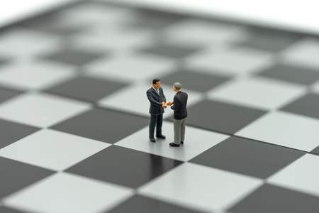 Miniature 2 people businessmen Shake hands on a chessboard with a chess piece on the back Negotiating in business. as background business concept and strategy concept with copy space. Standard-Bild - 114603442