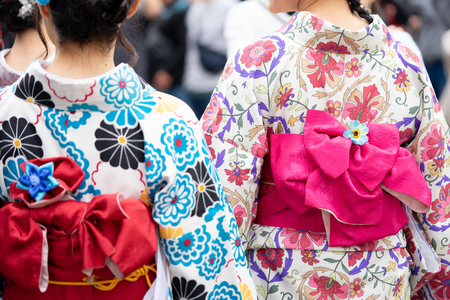 Young girl wearing Japanese kimono standing in front of Sensoji Temple in Tokyo, Japan. Kimono is a Japanese traditional garment. The word Фото со стока