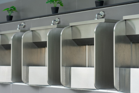 Public male bathroom is made of stainless steel for ease of cleaning, easy to produce, not broken. Concept of health, cleanliness Фото со стока