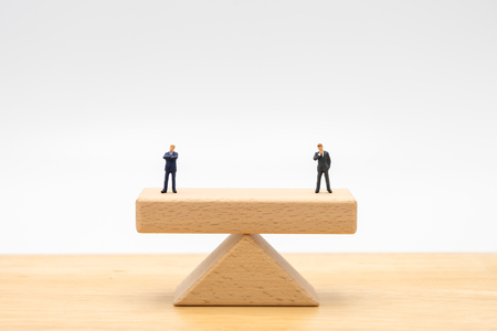 Miniature people businessmen Standing on wooden beams standing on both sides, weighing the importance of business concepts, maintaining benefits Conflict resolution