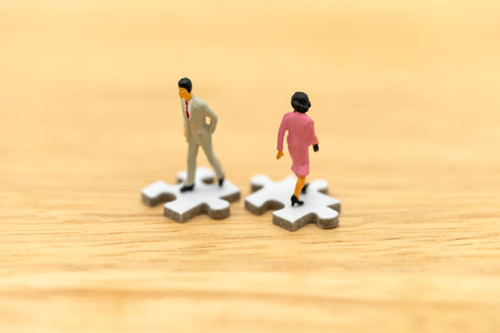 Miniature people businessmen standing on white Jigsaw. The concept used in selecting personnel to participate in the organization. with copy space.