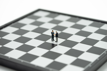 Miniature 2 people businessmen Shake hands on a chessboard with a chess piece on the back Negotiating in business. as background business concept and strategy concept with copy space.