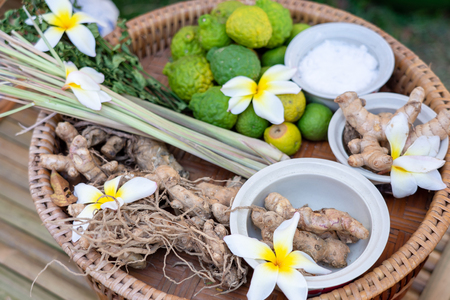 Local herbs of Thai ginger, galangal, kaffir lime, citronella, placed on a wooden tray, prepared for cooking, folk medicine, rubber latex treatment concepts