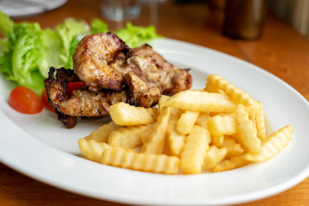 Grilled Pork and French Fries, arranged on a beautiful white food dish with salad vegetables, looking to eat Western main dishes. Popular with many Stock Photo