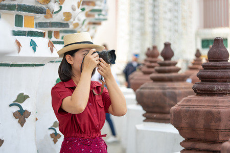 Beautiful woman tourist Held camera to capture the memories. Wat Arun Temple in Thailand. using as background  travel concept with copy spaces for your Stock Photo