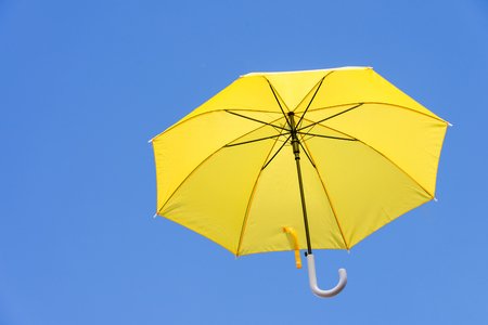 Yellow umbrellas floating in the sky, brightly blown by the wind, giving the feeling of freedom, safety. with copy spaces. Stock Photo