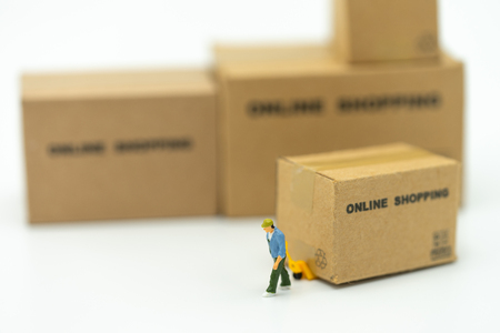 Miniature people Construction worker Online shopping with a shopping cart and shopping bags delivery service using as background shopping concept and delivery service concept with copy space Stock Photo
