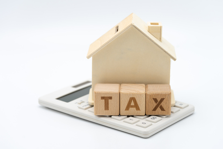 A model house model is placed on wood word TAX . as background property real estate concept with copy space for your text or  design. Banque d'images - 119520321