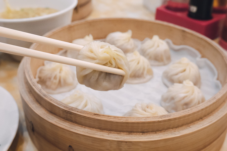 Xiao long bao soup dumpling buns with chopsticks in restaurant (Traditional Chinese food) in Taipei Taiwan Stok Fotoğraf