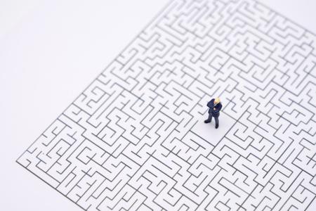 Miniatur-Geschäftsleute, die in der Mitte des Labyrinths stehen. Business Idea Concepts Fehlerbehebung Analyse von Problemen, um Lösungen zu finden. Standard-Bild